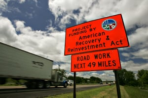 An orange traffic sign on the side of Interstate 94 leading to St. Cloud that says the next 49 miles are being repaired using funds from the American Recovery and Reinvestment Act. (Jason Wachter/ProPublica)