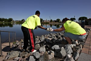 Abdiaziz Ali, 15, left, and Marissa Parmar, 17, members of the CareerOne program at the Minnesota WorkForce Center-St. Cloud, do landscaping and cleaning around Lake George in St. Cloud, Minn. in late June. (Jason Wachter/ProPublica)