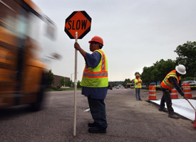 A road construction flagger slows traffic next to a road project funded by federal stimulus funds in Littleton, Colo. (Photo by John Moore/Getty Images)