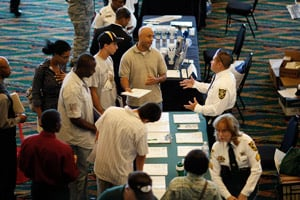 A man talks to a recruiter for the Broward Sheriff's department as he looks for a job during the RecruitMilitary Career Fair on Aug. 20 in Miami. (Joe Raedle/Getty Images)