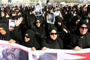 Hundreds of Bahraini protesters shout slogans as they attend the funeral of a fellow protester. (Photo by ADAM JAN/AFP/Getty Images)