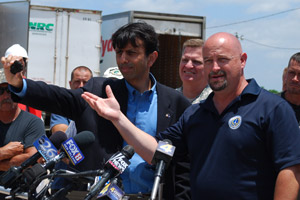 Louisiana Gov. Bobby Jindal, front left, holds up a tar ball while Bernard Parish President Craig Taffaro, front right, begs BP and the U.S. Coast Guard to deploy more booms to protect fragile wetlands at a press conference in Hopedale, La., on May 7, 2010. (Mira Oberman/AFP/Getty Images)