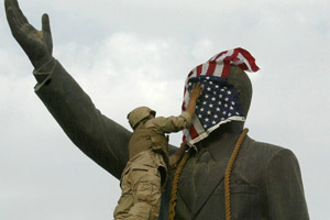 Wind blows a U.S. flag over the face of the Saddam Hussein statue as Marine Corporal Edward Chin affixes a chain around the statue's neck in Baghdad's Firdos Square on April 9, 2003. (Ramzi Haidar/AFP/Getty Images)
