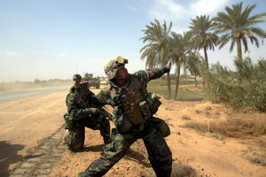 In a widely disseminated photograph, Lt. Col. Bryan McCoy throws a hand grenade on March 29, 2003, after his convoy was fired on outside a small village south of Baghdad, Iraq. (Robert Nickelsberg/Getty Images)