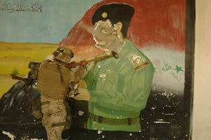 Lt. Col. Bryan McCoy uses a sledgehammer to deface a mural of Iraqi dictator Saddam Hussein at a military base a few miles from the center of Baghdad on April 9, 2003. (Photo courtesy of Peter Maass)