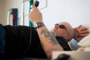 Sgt. William Fraas, who suffered brain damage from survived several roadside blasts in Iraq, checks the pressure gauge during exercises for his lower back at Mentis. (Blake Gordon/Aurora Photos)