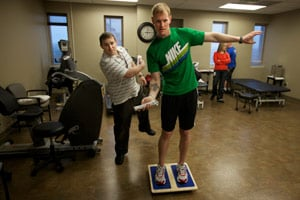 Brendan Jannesen is working on issues with his knee, playing Wii ping-pong while balancing on a balance board. Brian Smith, left, is a physical therapist working with veterans in the Share Program. (John W. Poole/NPR/Redux)