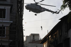 An Indian National Security Guard (NSG) commando swoops onto the rooftop of Nariman House at Colaba Market in Mumbai, India, on Nov. 28, 2008. (Pedro Ugarte/AFP/Getty Images)