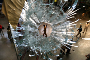 A policeman is seen through a bullet hole in the window of a restaurant at the central train station, Chhatrapati Shivaji Terminus, in Mumbai, India, on Dec. 2, 2008. (Uriel Sinai/Getty Images)
