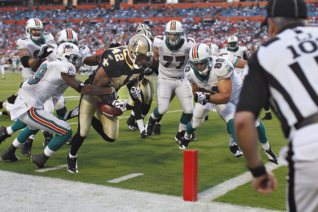 Darren Sharper scores a touchdown after making an interception against the  Miami Dolphins in 2009. (Simon Bruty Sports Illustrated) 4dd4b359d