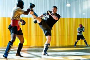 Sgt. First Class Kevin Rice, a master trainer at the U.S. Army Combatives School, drives back his partner with a high kick during a sparring session. (Pouya Dinat for NPR)