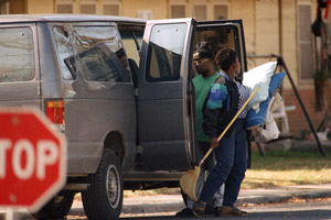 A woman exits a van before she enters a house in Vidor Village in Vidor, Texas, a historic center of Klu Klux Klan activity, on Jan. 13, 1994. HUD Secretary Henry Cisneros called in the U.S. Marshals, the FBI and police to escort four black adults and seven children into the buildings. (Hillary F. Hoffman/AP Photo)