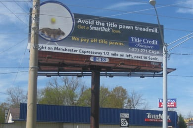 A billboard for Title Credit Finance above a TitleMax storefront shows a picture of a hamster on a wheel and urges borrowers to 'avoid the title pawn treadmill.' (Mitchell Hartman/Marketplace)