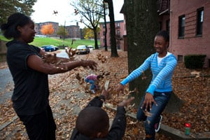 Cherie Michaux, left, with her daughter Ja'liza Michaux, 12, right, and son Ja'kye Brown, 7, center foreground, and her nephew Quaheem Moreau, 3, background, playing with leaves in Port Chester, N.Y., on Oct. 27. (Melanie Burford for ProPublica)
