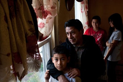 Vicente Ramos with his children in their home in New Brunswick, N.J., in March. Ramos recounted how he had to walk for three hours one night when the temp agency van didn't show. (Melanie Burford for ProPublica)