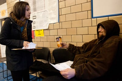 Community organizer Jasiela Chaves talks to temp worker Lorne Casey of Lawrence, Mass., inside a Labor Ready office about the state's Temporary Workers Right to Know Law that went into effect on Jan. 31, 2013. (Matthew Healey for ProPublica)