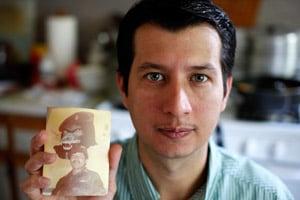 Oscar Ramírez Castañeda holds a photo of Lt. Oscar Ramírez Ramos who abducted him from Dos Erres after the massacre. (Matthew Healey for ProPublica)