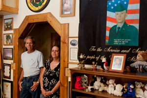Jim and Cindy Butler look into their living room, where they display photographs, tributes and medals awarded to their son Jake. (Steve Hebert for ProPublica)
