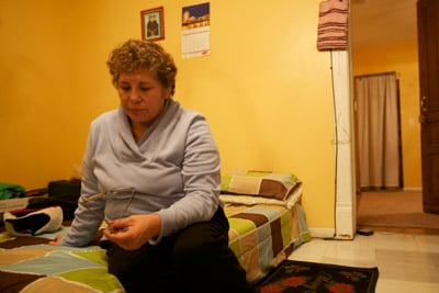 Rosa sits on the mattress in the room she rents with her boyfriend. The trap she sets for rats is visible on the floor near the door frame. (Sally Ryan for ProPublica)