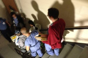 Staff at Bellevue Hospital carry a baby down a stairwell during the hospital's evacuation on Oct. 30, in New York. (Sheri Fink)