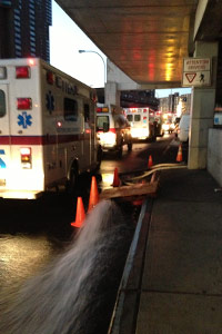 Water gushes out of a pump at Bellevue Hospital in New York as ambulances idle and wait for patients during the evacuation on Nov. 1. (Sheri Fink)