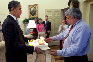 President Barack Obama presents a birthday cake to senior adviser Pete Rouse in the Oval Office. Rouse has been tapped by Obama to lead the administration in closing the military prison at Guantanamo, according to one senior official. (Official White House Photo by Pete Souza)
