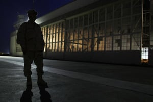 This photo, reviewed by the U.S. military, shows a military trooper standing in front of an old airplane hangar, before dawn, at Camp Justice, in July 2009. (Brennan Linsley/AFP/Getty Images)